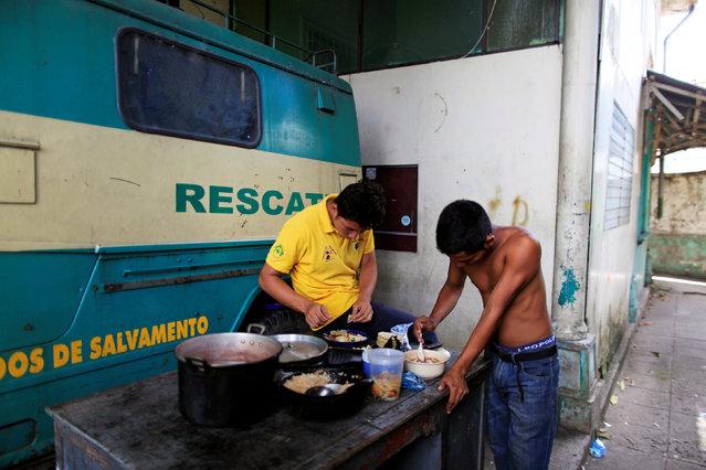 Rescuers eat lunch at the Comandos de Salvamento base in San Salvador, El Salvador August 17, 2016. (Photo by Jose Cabezas/Reuters)