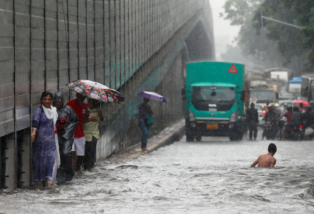 People wade through a waterlogged street during heavy rains in Mumbai, India July 9, 2018. (Photo by Danish Siddiqui/Reuters)