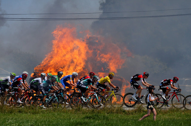 Riders pedal past haystacks that caught fire accidentally during the sixth stage of the 105 th edition of the Tour de France cycling race between Brest and Mur- de- Bretagne Guerledan, western France, on July 12, 2018. (Photo by Stephane Mahe/Reuters)