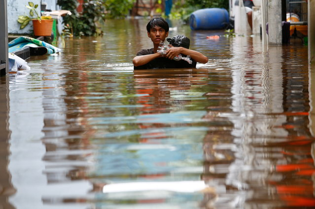 A man carrying his goods walks through the water in an area affected by floods, following heavy rains in Jakarta, Indonesia, February 20, 2021. (Photo by Ajeng Dinar Ulfiana/Reuters)