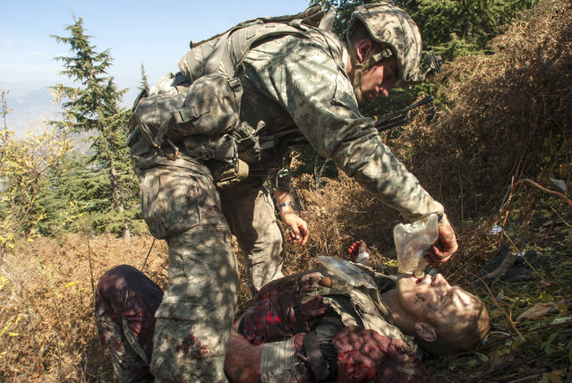 American soldiers with the 173rd Airborne Brigade Battle Company, on a battalion-wide mission in the Korengal Valley, looking for caves, weapons caches and known Taliban leaders, 2007. Tanner Stichter tends to Spc. Carl Vandeberge in the bushes moments after Vandeberge was shot in the stomach during a Taliban ambush, which killed one soldier and wounded two others. (Photo by Lynsey Addario)