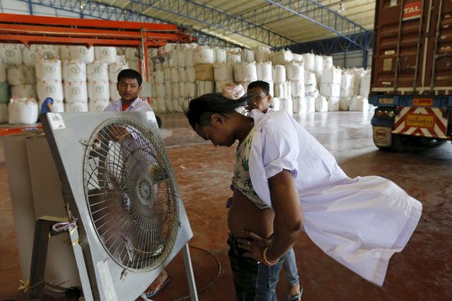 A worker refreshes himself with a fan after loading a container with rice bags at an export plant in the central Chainat province in Thailand, December 16, 2015. Picture taken December 16, 2015. (Photo by Jorge Silva/Reuters)