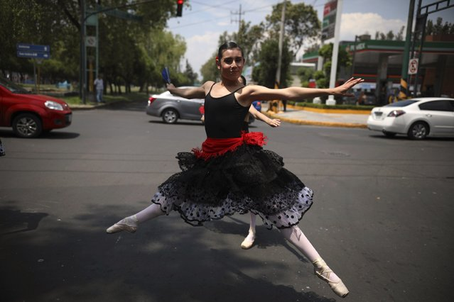 A ballerina dances at a traffic light stop, in Mexico City, Saturday, July 28, 2018. (Photo by Emilio Espejel/AP Photo)