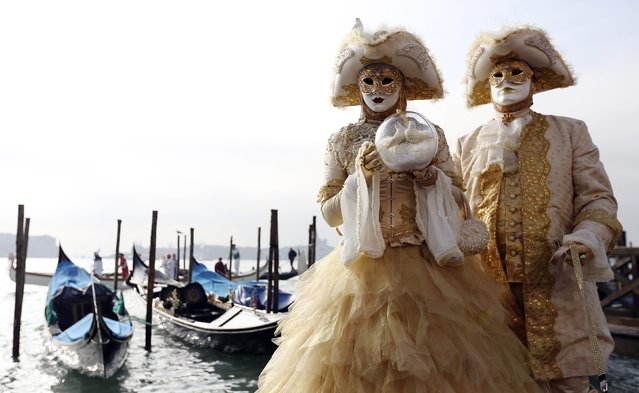 Masked revellers pose in front of St.Mark square during carnival, in Venice February 8, 2015. (Photo by Stefano Rellandini/Reuters)