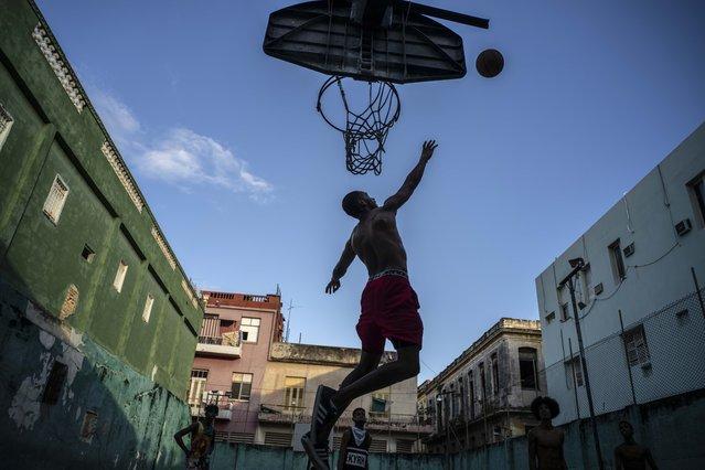 Men play basketball at a court in Havana, Cuba, Monday, December 21, 2020. (Photo by Ramon Espinosa/AP Photo)