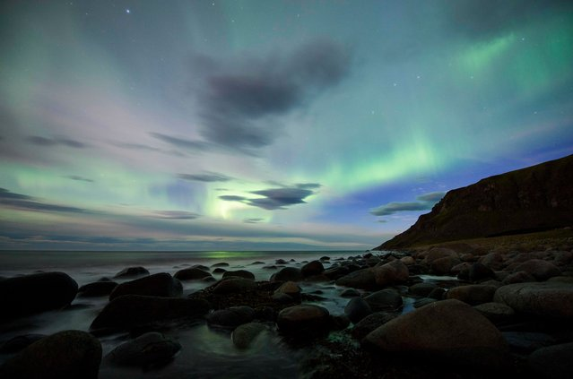 The northern lights, or aurora borealis, illuminate the sky over Flakstad beach on Lofoten Islands in the Arctic Circle on September 5, 2017. (Photo by Jonathan Nackstrand/AFP Photo)