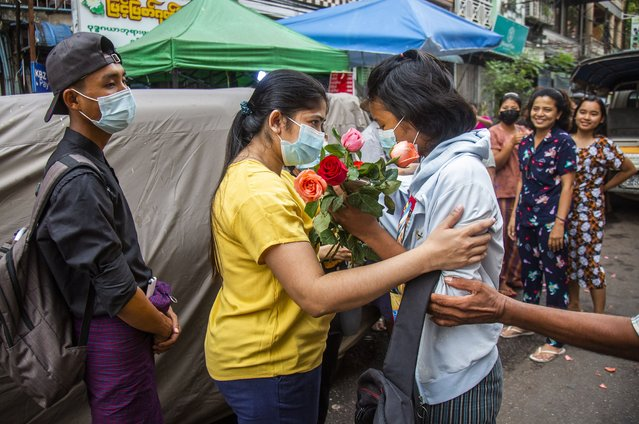 An anti-coup student protester is welcomed home with flowers by the residents of her neighborhood after being released from jail, Friday, March 26, 2021, in Yangon, Myanmar. (Photo by AP Photo/Stringer)