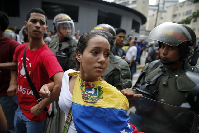 Opposition students march next to national guards during a march against President Nicolas Maduro's government in Caracas February 12, 2015. (Photo by Jorge Silva/Reuters)