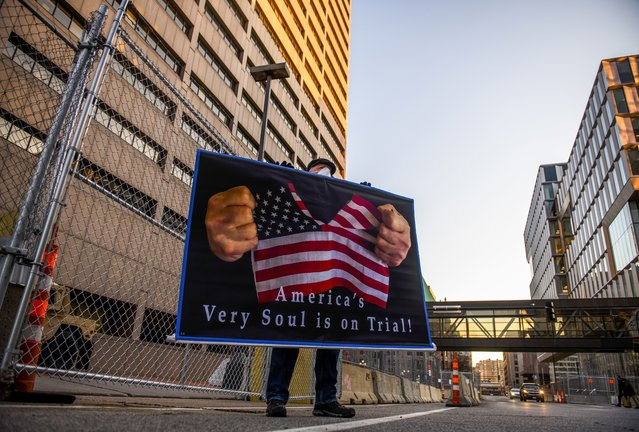 """Stephen Parlato holds a sign that reads """"America's very soul is on trial"""" outside the Hennepin County Government Center on March 29, 2021 in Minneapolis, Minnesota. Opening statements are set to begin today in the trial of former Minneapolis Derek Chauvin who is charged with multiple counts of murder in the death of George Floyd last May. (Photo by Stephen Maturen/Getty Images)"""
