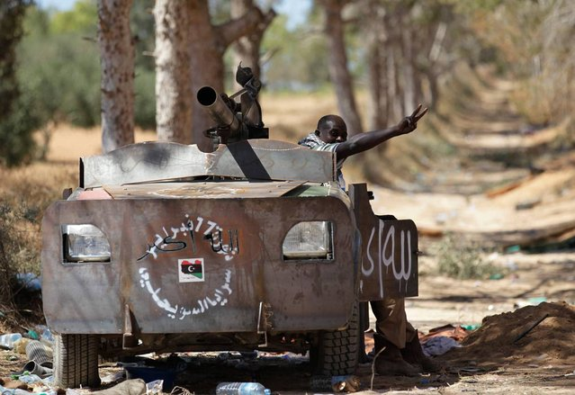 A Libyan rebel fighter, in a vehicle rigged with armor plating, flashes a victory sign at a territory taken from forces loyal to Muammar el-Qaddafi, after rebels pushed several kilometers in the direction of Zliten, west of the rebel-held port city of Misurata, on June 13, 2013. (Photo by Zohra Bensemra/Reuters)