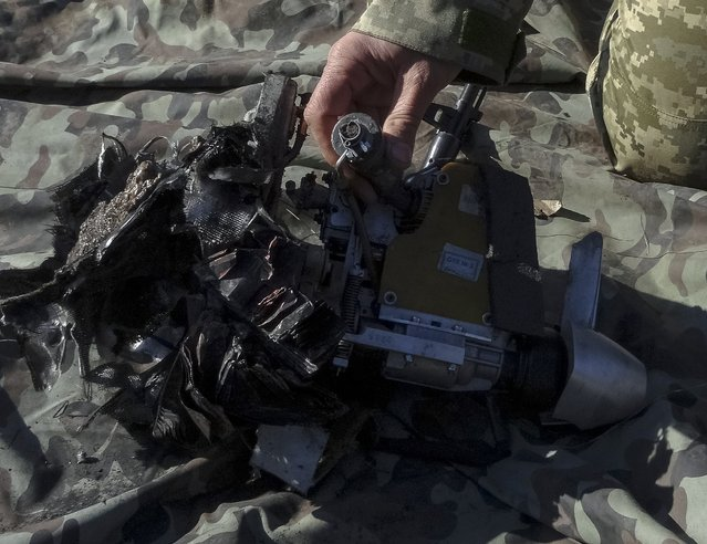 A member of the Ukrainian armed forces shows the remains of an unmanned aerial vehicle, which was recently downed, in Kramatorsk, Donetsk region, February 12, 2015. (Photo by Reuters/Stringer)