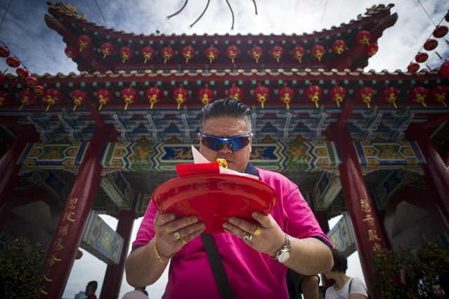 A Malaysian prays on the first day of Chinese Lunar New Year at a temple in Kuala Lumpur, Malaysia on Thursday, February 19, 2015. (Photo by Joshua Paul/AP Photo)