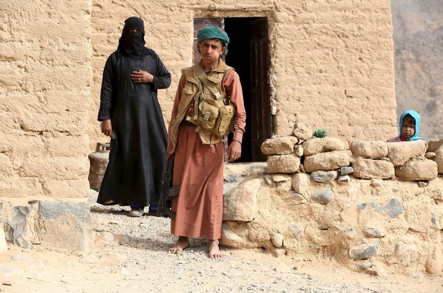 A tribal fighter loyal to Yemen's government stands outside a house in Al Khurais village of Nihm district east of the capital Sanaa January 11, 2016. (Photo by Ali Owidha/Reuters)