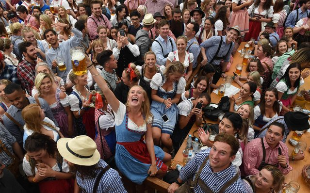 Visitors drink beer during the 185th Oktoberfest, Munich's annual beer festival, on September 22, 2018 in Munich, southern Germany. The world's largest beer festival is held from September 22 until October 7, 2018. (Photo by Christof Stache/AFP Photo)