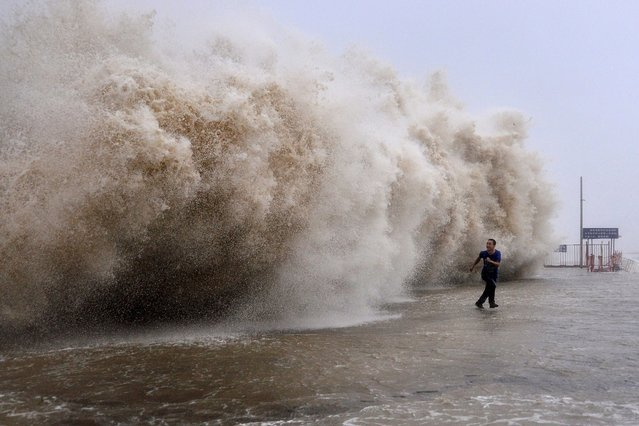 This photo taken on September 22, 2013 shows a man running away from a huge wave pushed up by Typhoon Usagi on a wharf in Shantou, China. (Photo by AFP Photo)