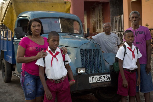 In this September 23, 2013 photo, 11-year-old twin brothers Arian and Adrian Cueto pose for portraits in their school uniforms alongside their parents and grandfather as they gather around their family's truck in Havana, Cuba. The Cueto twins are one of 12 sets of twins living along two consecutive blocks in western Havana, ranging in age from newborns to senior citizens. (Photo by Ramon Espinosa/AP Photo)