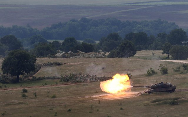 """A military tank from the Greek army fires during the """"Strike Back 21"""" military drill in Koren training grounds, Bulgaria, June 4, 2021. Armed personnel from Greece, Romania and Bulgaria take part in the drill. (Photo by Stoyan Nenov/Reuters)"""