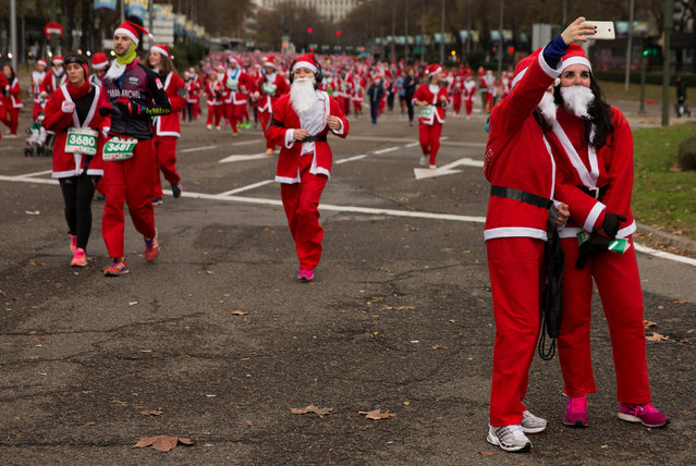 Participants, wearing Santa Claus outfits, take a selfie during a charity race in benefit of the Multiple Sclerosis Foundation in Madrid, Spain, December 17, 2016. (Photo by Sergio Perez/Reuters)