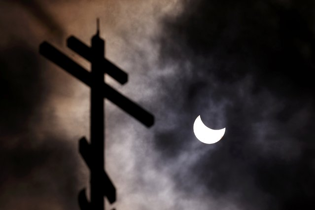 A partial solar eclipse forms in the sky through clouds near the cross of the Church of St Nicholas the Miracle-Maker in Sofia March 20, 2015. A partial eclipse was visible on Friday, the first day of northern spring, across parts of Africa, Europe and Asia. The total eclipse of the sun was only be visable in the Faroe Islands and the Norwegian archipelago of Svalbard in the Arctic Ocean. (Photo by Stoyan Nenov/Reuters)