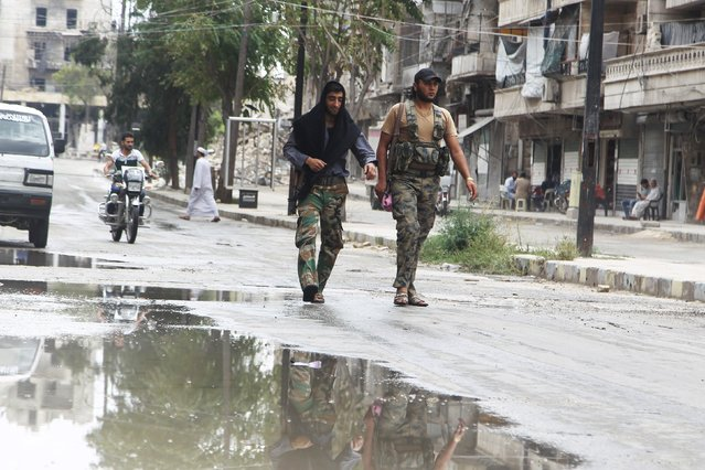 Free Syrian Army fighters carry their weapons as they walk along a street in a rebel-controlled area of Aleppo, Syria, August 30, 2015. (Photo by Abdalrhman Ismail/Reuters)