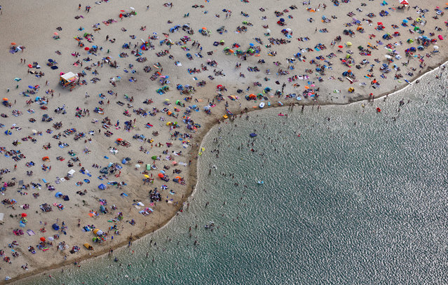People at a beach on the shores of lake Silbersee (Silver Lake) during a long-lasting heatwave in Haltern, Germany, August 4, 2018. (Photo by Wolfgang Rattay/Reuters)