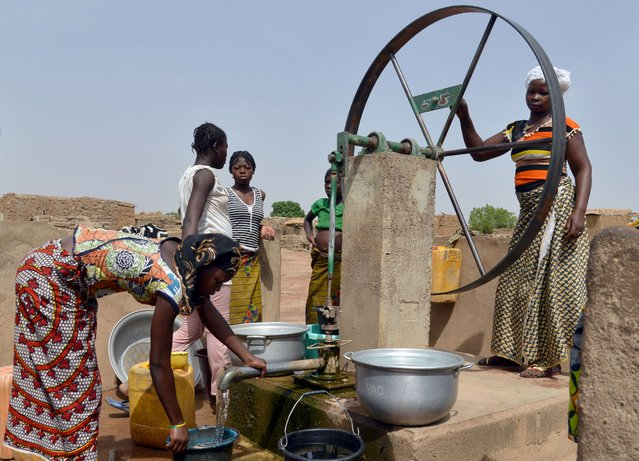 Women fetch water at a pump in the village of Kalembouly, Burkina Faso, on March 27, 2015. (Photo by Issouf Sanogo/AFP Photo)