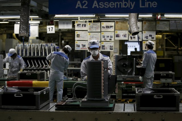 Daikin Industries Ltd employees work the production line of outdoor air conditioning units at the company's Kusatsu factory in Shiga prefecture, western Japan March 20, 2015. (Photo by Yuya Shino/Reuters)