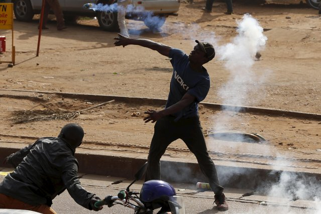 A supporter of Uganda's leading opposition party Forum for Democratic Change (FDC) throws a tear gas canister fired by the police as police and military forces disperse their procession with their presidential candidate to a campaign ground, in Kampala, Uganda, February 15, 2016. (Photo by James Akena/Reuters)