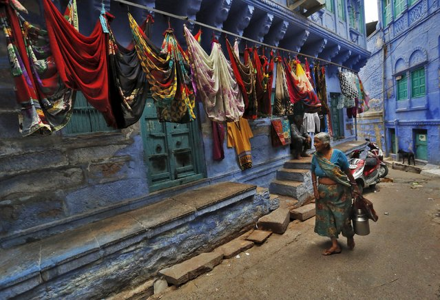 A woman walks past a shop selling sarees, traditional Indian cloth used for women's clothing, along an alley at Jodhpur in Rajasthan, April 6, 2015. (Photo by Adnan Abidi/Reuters)