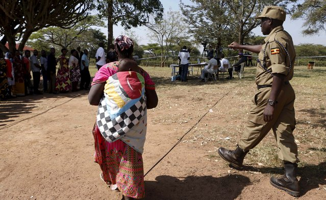 A policeman directs a mother at a polling station during the presidential elections in Kirihura in western Uganda, February 18, 2016. (Photo by James Akena/Reuters)