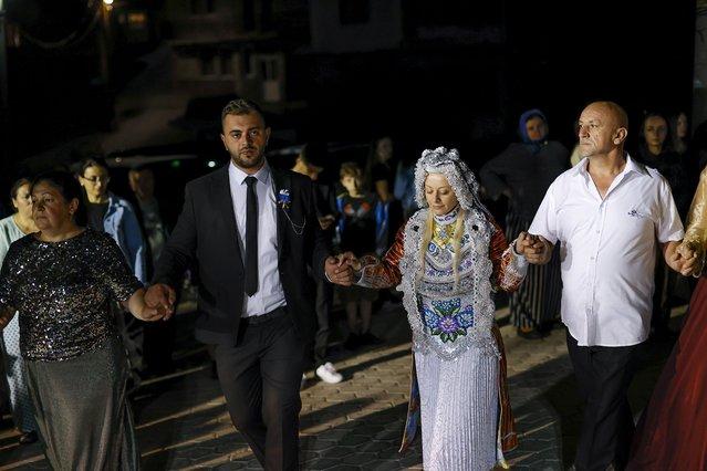 A Kosovar Bosnian bride Sellma Demirovic (C-R) and the bridegroom Fejad Karadollami (C-L) dance during the traditional wedding ceremony in the village of Donje Ljubinje, Kosovo, 14 August 2021. (Photo by Valdrin Xhemaj/EPA/EFE)