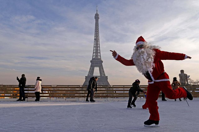 A man dressed as Santa Claus skates on an ice rink across from the Eiffel Tower on December 12, 2013. (Photo by Jacky Naegelen/Reuters)