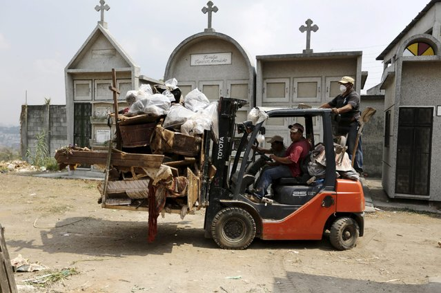 Grave cleaners transport discarded coffins and corpses wrapped in plastic bags on a forklift during exhumation works  at the General Cemetery in Guatemala City, April 15, 2015. (Photo by Jorge Dan Lopez/Reuters)