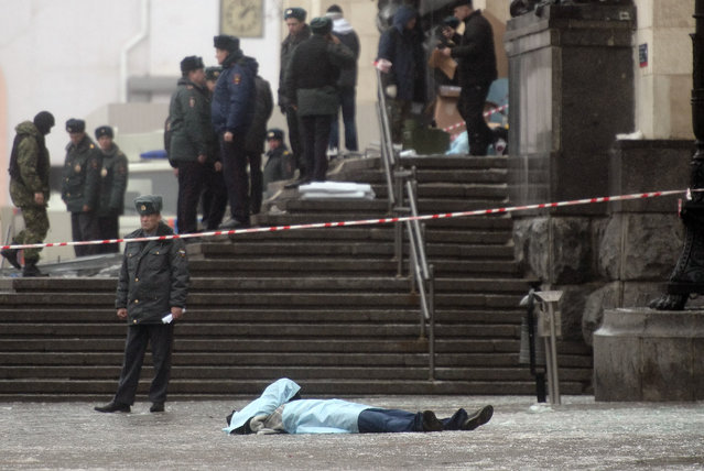 The body of a victim lies at the site of a bomb explosion at the entrance to Volgograd railway station in Volgorgrad, Russia, 29 December 2013. At least 14 people were killed and 50 injured when a female suicide bomber blew herself up at the main railway station in the southern Russian city of Volgograd. The blast raised fears about terrorism attacks some six weeks before the opening of the Winter Olympic Games in the Black Sea resort of Sochi, some 700 kilometres south of Volgograd.  (Photo by EPA/STR)