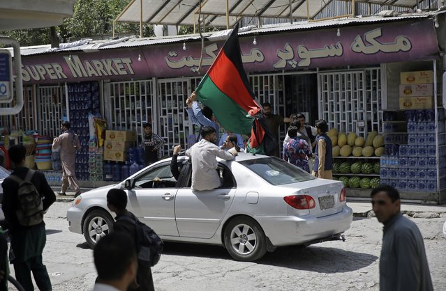 Afghans wave a black, red and green banner in honor of the Afghan flag – a banner that is becoming a symbol of defiance since the Taliban have their own flag, on Afghan Independence Day, in Kabul, Afghanistan, Thursday, Aug. 19, 2020. On Thursday, a procession of cars and people near Kabul's airport carried long black, red and green banners in honor of the Afghan flag – a banner that is becoming a symbol of defiance since the militants have their own flag. (Photo by Rahmat Gul/AP Photo)