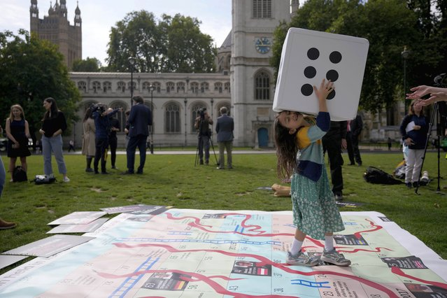 """Gabriella, the seven year old daughter of imprisoned British-Iranian Nazanin Zaghari-Ratcliffe, joins in a game on a giant snakes and ladders board in Parliament Square, London, to show the """"ups and downs"""" of Zaghari-Ratcliffe's case to mark the 2,000 days she has been detained in Iran, Thursday, September 23, 2021. Zaghari-Ratcliffe was originally sentenced to five years in prison after being convicted of plotting the overthrow of Iran's government, a charge that she, her supporters and rights groups deny. While employed at the Thomson Reuters Foundation, the charitable arm of the news agency, she was taken into custody at the Tehran airport in April 2016 as she was returning home to Britain after visiting family. (Photo by Matt Dunham/AP Photo)"""