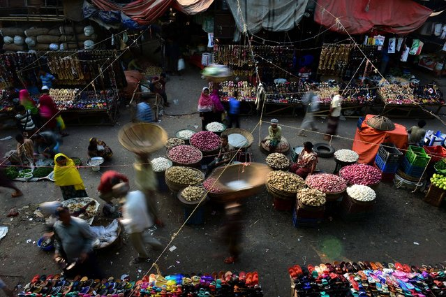 Bangladeshi vegetable vendors wait for customers at a wholesale market in Dhaka on January 22, 2017. Dhaka Kawran Bazar is a major business district and wholesale market place in Dhaka. (Photo by AFP Photo/Stringer)