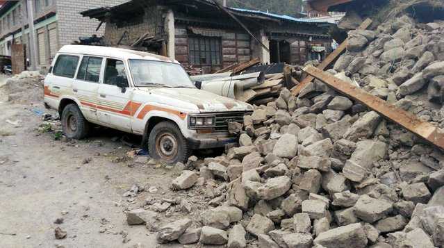 A car is seen next to a collapsed house, after a 7.9 magnitude earthquake hit Nepal, in Xigaze Prefecture, Tibet Autonomous Region, China, April 25, 2015. (Photo by Reuters/Stringer)