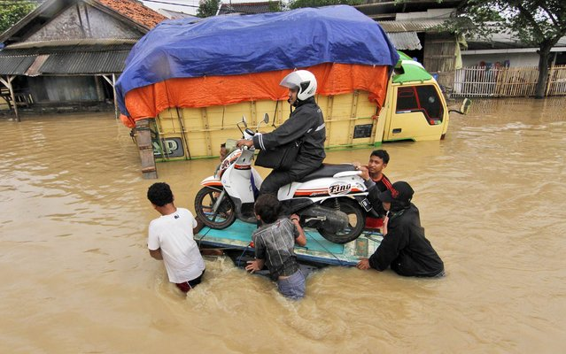 Indonesian men help a motorist to cross a flooded street on a raft in Pamanukan, Indonesia, Monday, January 20, 2014. Seasonal rains and high tides in recent days have caused widespread flooding across much of Indonesia. (Photo by AP Photo/Kusumadireza)