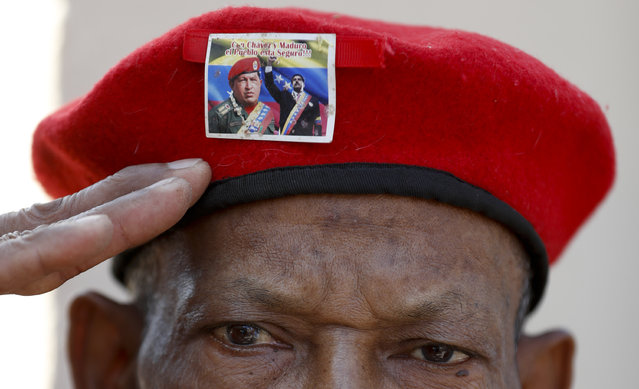A man wearing the iconic red beret of Venezuela's late President Hugo Chavez, featuring a photo of current President Nicolas Maduro with Chavez, salutes as he waits to enter the Historic Military Museum to visit the leader's remains on the sixth anniversary of his death in Caracas, Venezuela, Tuesday, March 5, 2019. Chavez, who died of cancer, continues to unleash mixed feelings among Venezuelans: some remember him as the father of a revolution that defended the poor, while others blame him for the deep and prolonged crisis that overwhelms the South American country. (Photo by Eduardo Verdugo/AP Photo)