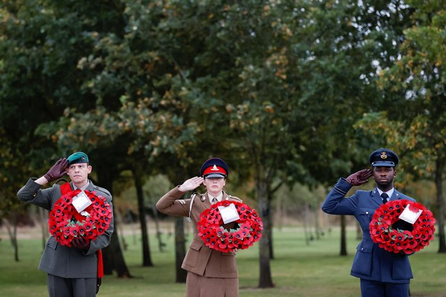 Members of military hold wreaths during a memorial service at the Camp Bastion Memorial at the National Memorial Arboretum in Staffordshire, Britain, October 7, 2021. (Photo by Phil Noble/Reuters)
