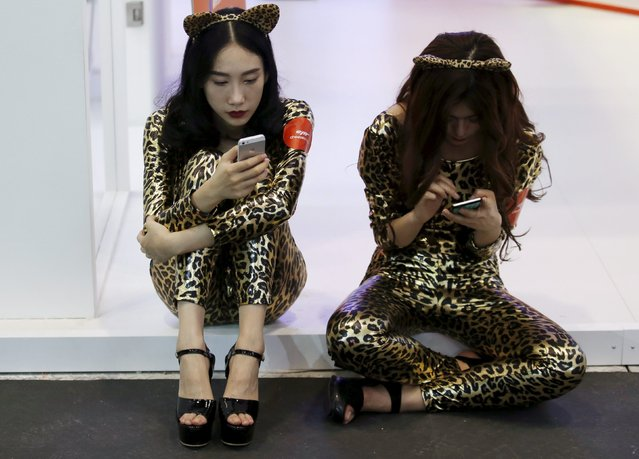 Promotional staff use mobile phones during their break at the Global Mobile Internet Conference (GMIC) 2015 in Beijing, China, April 28, 2015. (Photo by Kim Kyung-Hoon/Reuters)