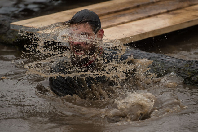 """A competitor takes on a water obstacle as he takes part part in the """"Tough Guy"""" adventure race near Wolverhampton, central England, on January 29, 2017. (Photo by Oli Scarff/AFP Photo)"""