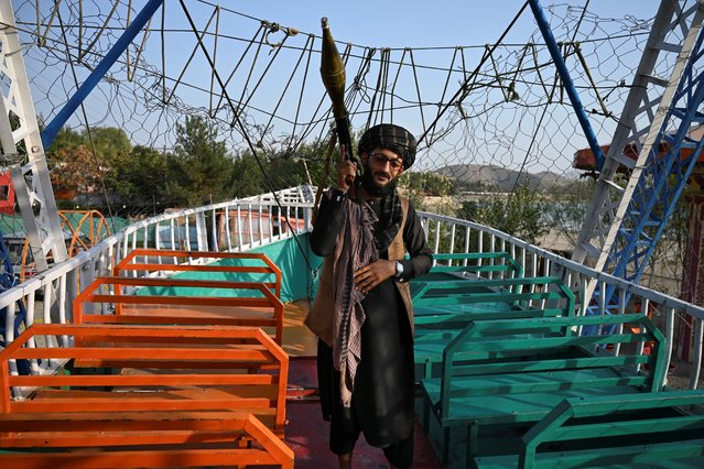 """In this photograph taken on September 28, 2021 a Taliban fighter carrying a rocket propelled grenade (RPG) launcher stands on pirate ship ride in a fairground at Qargha Lake on the outskirts of Kabul. """"This is Afghanistan!"""" a Taliban fighter shouts on the pirate ship ride at a fairground in western Kabul, as his armed comrades cackle and whoop on board the rickety attraction. (Photo by Wakil Kohsar/AFP Photo)"""