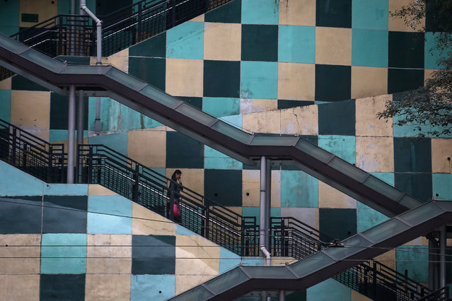 A woman walks down a set of stairs from a housing estate in Hong Kong on March 17, 2019. (Photo by Vivek Prakash/AFP Photo)