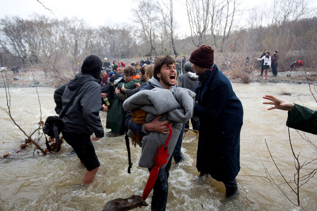 Migrants try to cross a river after leaving  the Idomeni refugee camp on March 13, 2016 in Idomeni, Greece. (Photo by Matt Cardy/Getty Images)