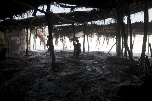 A man looks on as waves damage tourist huts at El Majahual beach in La Libertad May 3, 2015. El Salvador emergency authorities declared a green alert along the pacific coats due to a large swell that affected the Salvadoran coast and originated from the extra-tropical storms that formed in New Zealand and the Southern hemisphere, according to El Salvador's ministry of environment and natural resources. (Photo by Jose Cabezas/Reuters)