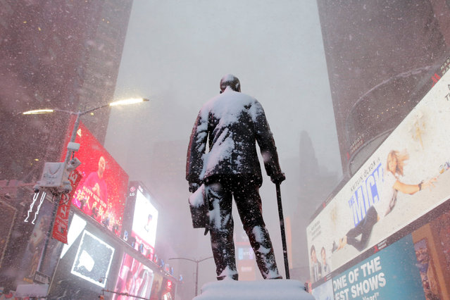 A statue of American composer, playwright, actor, and producer George M. Cohan stands in Times Square as snow falls in Manhattan, New York, U.S. February 9, 2017. (Photo by Andrew Kelly/Reuters)