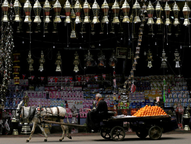 "An orange seller rides a donkey-drawn cart past traditional Ramadan lanterns called ""fanous"" displayed for sale at a stall in Cairo, Egypt April 3, 2019. (Photo by Amr Abdallah Dalsh/Reuters)"