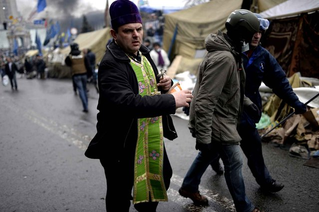 A priest rushes to give the last sacraments to an anti-government protester during clashes with riot police in central Kiev on February 20, 2014 in Kiev. (Photo by Bulent Kilic/AFP Photo)